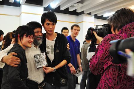 孟加拉著名摄影师Shahidul(左二)来我院开展工作坊,学生在作品展览现场与他合影